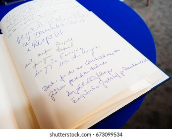 STRASBOURG, FRANCE - JUL 1, 2017: The messages in diverse languages of high ranked officials on the book of condolences next to a portrait former German Chancellor Helmut Kohl at European Parliament.