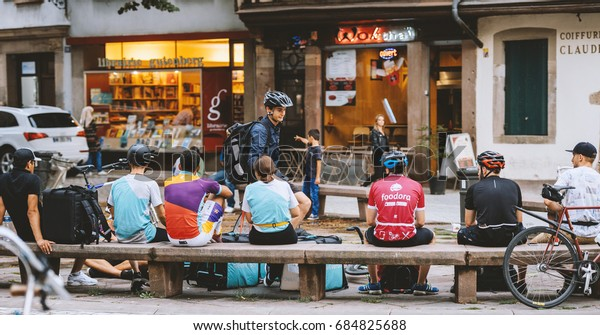 STRASBOURG, FRANCE - JUL 12, 2017: Deliveroo, Foodora and Uber Eats employees resting near their bikes eating lunch in city center ready to deliver on time the food to the client.