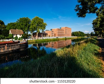 STRASBOURG, FRANCE - JUL 18,  2018: Future Embassy of Turkey building in Strasbourg on Quai Jacoutot Ill River with cargo transportation barge and pedestrians commuting on the summer evening