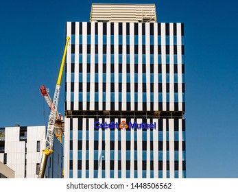 Strasbourg, France - Jul 2 2019: French Credit Mutuel cooperative bank, logotype on the new headquarter in Wacken business district in central Strasbourg - construction crane