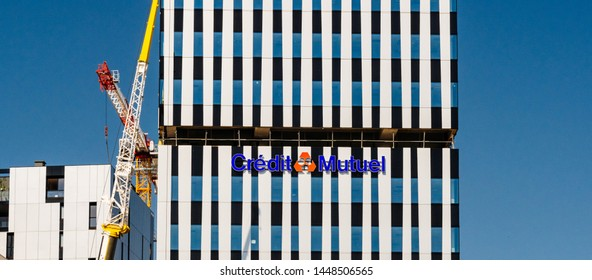 Strasbourg, France - Jul 2 2019: Wide image French Credit Mutuel cooperative bank, logotype on the new headquarter in Wacken business district in central Strasbourg - construction crane