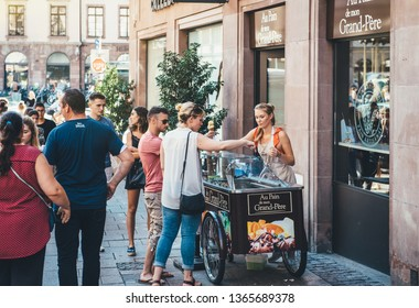 Strasbourg, France - Jul 22, 2017: Young blonde woman serving customer with french bio home-made ice-cream parlor in central Strasbourg France horizontal image