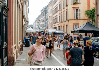 Strasbourg, France - Jul 8, 2017: Large group of people walking on the pedestrian street in central old city with food truck selling vans delicious French and international food and drinks