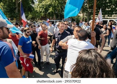 STRASBOURG, FRANCE - JULY 11, 2015: Police use force to prevent clash while Uyghur human rights activists participate in a demonstration to protest against Chinese government's policy in Uyghur