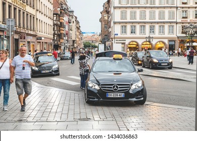 Strasbourg, France - July 22, 2017: Luxury Mercedes-Benz E klasse taxi in central Place Gutenberg with driver helping customers to lead luggage in trunk