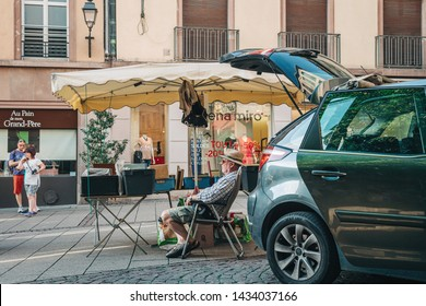 Strasbourg, France - July 22, 2017: Senior man with hat sitting in chair relaxed waiting for customers to buy used books at daily flea market in central Strasbourg