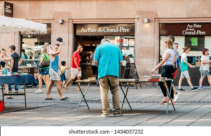 Strasbourg, France - July 22, 2017: Pedestrians walking on French street with senior man arranging used books at flea market in central part of the city