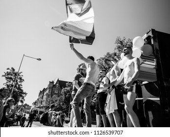 STRASBOURG, FRANCE - JUN 10, 2017: Young male gay men people dancing waving rainbow flag at Lesbian Gay Bisexual Transgender LGBT visibility march pride Festigays