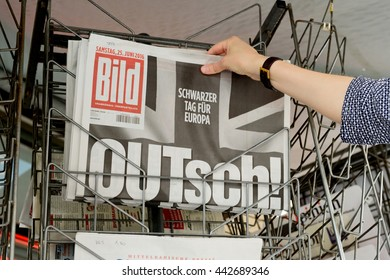 STRASBOURG, FRANCE - JUN 25, 2016: Woman buying Bild Magazine newspaper with shocking headline titles at press kiosk about the Brexit requesting to quit the European Union
