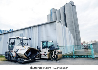 Strasbourg, France - Mar 10, 2021: Side view of Vogele Wirtgen group SUPER 1800-3 most powerful tracked paver a part of John Deere and asphalt paver with tall industrial factory building background