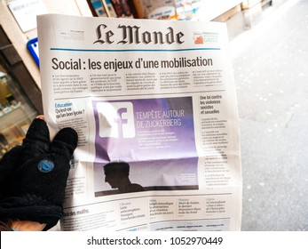 STRASBOURG, FRANCE  - MAR 22, 2018: Man reading buying Le Monde newspaper at press kiosk featuring Mark Zuckerberg, Facebook CEO - scandat data leaks from Cambridge Analytica