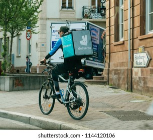 STRASBOURG, FRANCE - MAY 18, 2018: Fast Deliveroo cyclist with distinct bag driving fast on the street to arrive at the client with fresh and hot food