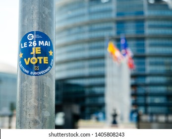 Strasbourg, France - May 23, 2019: I vote sticker on street sign pole with all European union member states flags waving in front of the building 2019 European Parliament election