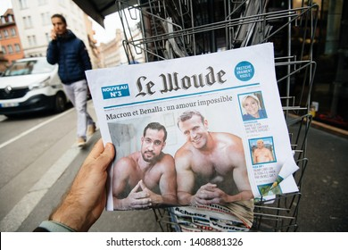 Strasbourg, France - May 27, 2019: Man holding buying satirical newspaper Le Wonde with Emmanuel Macron and Alexandre Benalla on cover