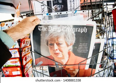 Strasbourg, France - May 27, 2019: Man holding buying newspaper The Daily Telegraph front page on street press kiosk newsstand with the Theresa May crying announcing resignation