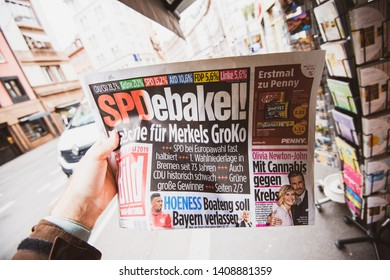 Strasbourg, France - May 27, 2019: Man holding buying Die Bild newspaper front page on street press kiosk newsstand with the results of 2019 European Parliament election in Germany