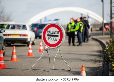 STRASBOURG, FRANCE - NOV 14 2015: French Police checking vehicles on the 'Bridge of Europe' between Strasbourg and Kehl Germany, as a security measure in the wake of attacks in Paris - slow down sign