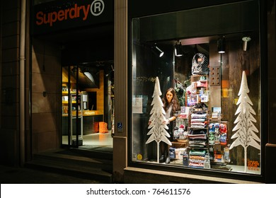 STRASBOURG, FRANCE - NOV 21, 2017: Female seller arranging preparing for the upcoming winter holidays the white fur trees and other Christmas decorations in display windows of a clothing shop SUPERDRY