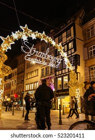 STRASBOURG, FRANCE - NOV 28, 2015: Police officers surveilling the entrance gate with neon Christmas decorations of the Christmas Market in Strasbourg with high grade security after Paris attacks
