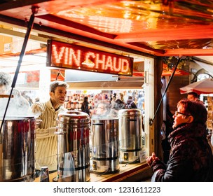 STRASBOURG, FRANCE - NOV 29, 2017: happy French woman buying mulled wine from Market stall in the evening during Strasbourg Christmas Market in Place de la Cathedrale, Alasace