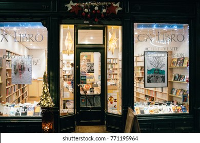 STRASBOURG, FRANCE - NOV 29, 2017: EX Libro Library bookstore at night in Strasbourg selling used books with pedestrians walking in front looking at window store