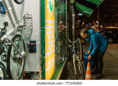STRASBOURG, FRANCE - NOV 29, 2017: Man pump changing bicycle wheel at bike store in France at dusk