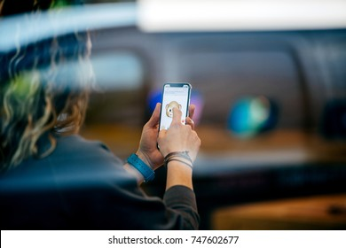 STRASBOURG, FRANCE - NOV 3, 2017: Street reflection of latest Apple iPhone X goes on sale in Apple Store worldwide with woman trying the fun Animoji, laugh Face ID
