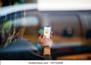 STRASBOURG, FRANCE - NOV 3, 2017: Woman using Animoji with Cat face on the latest Apple iPhone X in Apple Store