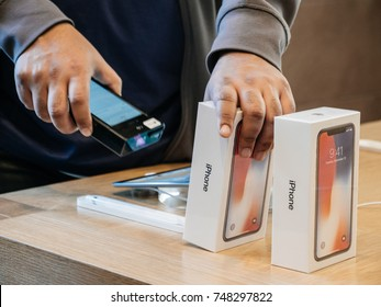 STRASBOURG, FRANCE - NOV 3, 2017: Seller scanning barcode of the latest iPhone X 10 smartphone before purchase at Apple Store Computers