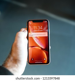 STRASBOURG, FRANCE - OCT 26, 2018: Customer POV holding new red iPhone XR smartphone during the launch day notification price app