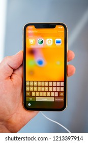 STRASBOURG, FRANCE - OCT 26, 2018: Customers holding admiring testing latest yellow iPhone XR smartphone in Apple Store Computers during the launch day apps, siri, search field