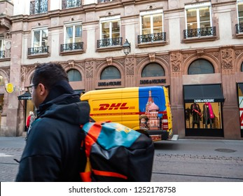 STRASBOURG, FRANCE - OCT 26, 2018: People walking in front of DHL Deutsche Post yellow delivery van parked on the street in France in front of the luxury fashion clothes store Zadig and Voltaire -