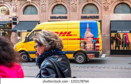 STRASBOURG, FRANCE - OCT 26, 2018: Pedestrians walking in front of DHL Deutsche Post yellow delivery van parked on the street in France in front of the luxury fashion clothes store Zadig and Voltaire