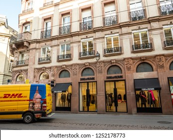 STRASBOURG, FRANCE - OCT 26, 2018: DHL Deutsche Post yellow delivery van parked on the street in france in front of the luxury fashion clothes store Zadig and Voltaire
