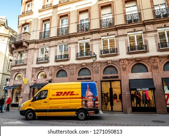 STRASBOURG, FRANCE - OCT 26, 2018: leaving DHL Deutsche Post yellow delivery van France in front of the luxury fashion clothes store Zadig and Voltaire - Moscow sticker on the van