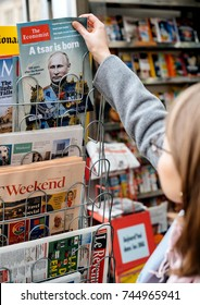 STRASBOURG, FRANCE - OCT 28, 2017: Woman buying The Economist magazine at press kiosk featuring Vladimir Putin on cover and headline A Tsar is Born