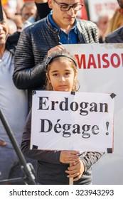 STRASBOURG, FRANCE - OCT 4, 2015 Demonstrators protesting against Turkish President Recep Tayyip Erdogan's visit to Strasbourg - young girl holding Erdogan, leave! placard