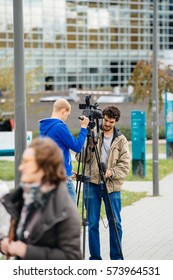 STRASBOURG, FRANCE - OCT 7, 2016: Rear view of journalist cameraman reporter transmitting live front European Parliament building official Presidential visit with flags waving and people protesting