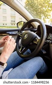 STRASBOURG, FRANCE - SEP 15, 2018: Focus on the SKODA logotype as woman drives in the the modern Superb Czech car tilt-shift lens