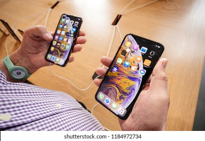 STRASBOURG, FRANCE - SEP 21, 2018: Apple Store with senior man customer POV comparing the new latest iPhone Xs and Xs Max smartphones telephones by the Cupertino geant