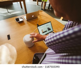 STRASBOURG, FRANCE - SEP 21, 2018: Curious senior man Point of view testing HomePod the smart speaker in Apple Store - next is as powerful Apple MacBook pro laptop