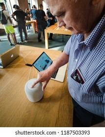 STRASBOURG, FRANCE - SEP 21, 2018: Side view of curious senior man testing HomePod the smart speaker in Apple Store with customers in background
