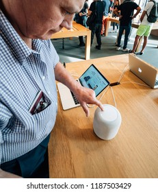 STRASBOURG, FRANCE - SEP 21, 2018: Curious senior man testing HomePod the smart speaker in Apple Store during the iPhone Xs and Xs Max preorder for Xr and Watch Series 4 wearable smartwatch