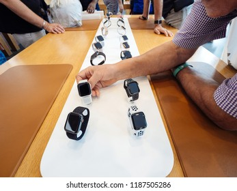 STRASBOURG, FRANCE - SEP 21, 2018: Side view of curious senior man testing the Aluminum Apple Watch Series 4 GPS LTE smartwatch in Apple Store with customers silhouettes in background