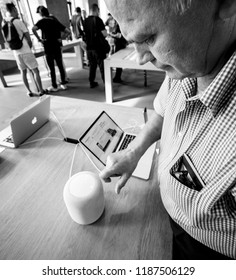 STRASBOURG, FRANCE - SEP 21, 2018: Curious senior man testing HomePod the smart speaker in Apple Store during the iPhone Xs and Xs Max for Xr and Watch Series 4 wearable smartwatch - black and white
