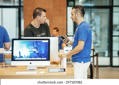 STRASBOURG, FRANCE - SEPTEMBER 19, 2014: An Apple Inc. genius employee assists a customer with the purchase during the sales launch of the iPhone 6 and iPhone X Plus at the company's store in France.