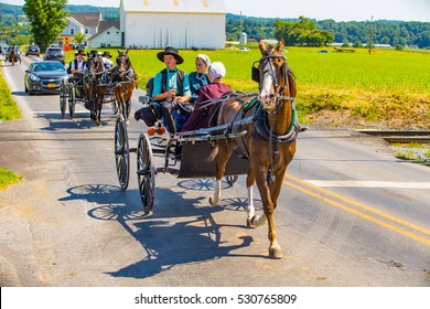 Strasburg, PA - June 19, 2016: Amish using horse drawn buggies on a county road in Lancaster County, PA.