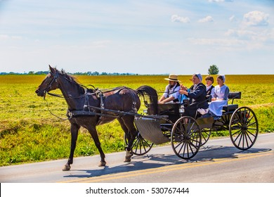 Strasburg, PA â?? June 19, 2016: An Old Order Amish family ride in an open wagon in Lancaster County, Pennsylvania.