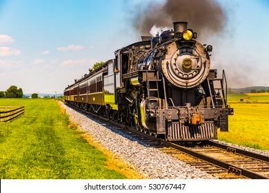 Strasburg. PA - June 19, 2016: Strasburg Rail Road Locomotive 90 pulls passenger cars through Lancaster County pastures.