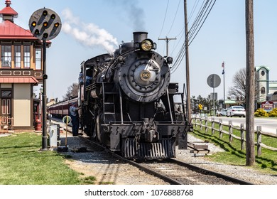 Strasburg, PA, USA - April 14, 2018:  A smokey steam locomotive operated by the Strasburg Rail Road pulls into the train station in Lancaster County, PA.